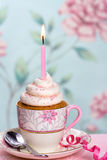 Birthday cupcake. Pink birthday cupcake in a teacup Royalty Free Stock Photo