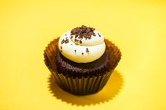 Birthday cupcake against a yellow background.  Stock Photo