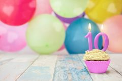 Birthday cupcake with balloons in the background Stock Photo