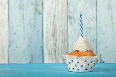 Birthday cupcake. With blue candle and blue background Stock Photo