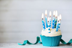 Birthday cupcake. Cupcake with blue birthday candles royalty free stock photography
