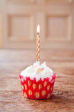 Birthday cupcake blurry background with  lit candle Royalty Free Stock Photography