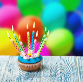 Birthday cupcake. With burning candles on the background of balloons Stock Photography