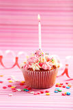 Birthday cupcake with butter cream and candle on colorful background Stock Photo