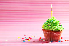 Birthday cupcake with butter cream and candle on colorful background. Birthday cupcake with a butter cream and candle on colorful background Royalty Free Stock Images
