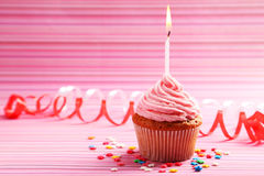 Birthday cupcake with butter cream and candle on colorful background Stock Photography