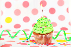 Birthday cupcake with butter cream and candle on colorful background Royalty Free Stock Image