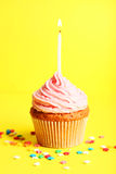 Birthday cupcake with butter cream and candle on yellow background Royalty Free Stock Images