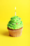 Birthday cupcake with butter cream and candle on yellow background Royalty Free Stock Photography
