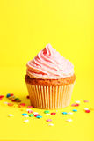 Birthday cupcake with butter cream on yellow background Stock Image