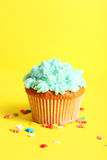 Birthday cupcake with butter cream on yellow background Royalty Free Stock Images