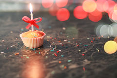 Birthday cupcake with a candle bokeh Royalty Free Stock Photos