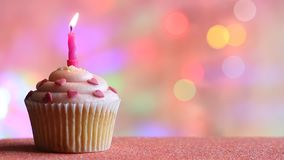 Birthday cupcake and candle on colorful defocused background party concept. Closeup stock video