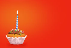 Birthday cupcake with candle. On orange background.Text space Royalty Free Stock Photography