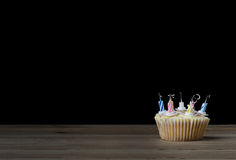 Birthday Cupcake with Candles Blown Out on Black Royalty Free Stock Photo