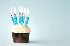 Birthday cupcake. Cupcake decorated with birthday candles royalty free stock photography