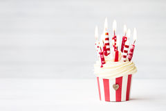 Birthday cupcake. Cupcake decorated with red and white candles Royalty Free Stock Photo
