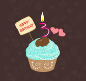 Birthday cupcake with lit candle in shape of number three. Birthday cupcakes against a cyan background Royalty Free Stock Photo