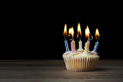 Birthday Cupcake with Lit Candles on Black Royalty Free Stock Images