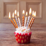 Birthday cupcake with lots of lit candles Stock Photography