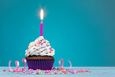 Birthday Cupcake. Cupcake with pink birthday candle and sprinkles over a blue background Stock Photo