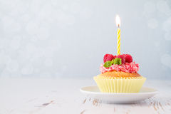 Birthday cupcake with raspberry and candy Stock Photos