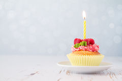 Birthday cupcake with raspberry and candy Stock Photo