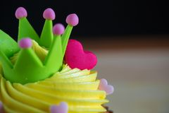 Birthday cupcake with a single blue candle.Cupcake with yellow cream and heart for love valentines. Stock Photos