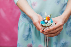 Birthday cupcake with single candle in female hands. Holiday concept, greeting card design Stock Photos