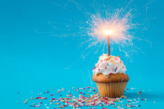 Birthday Cupcake with a sparkler. On blue background Royalty Free Stock Photo