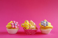 Birthday cupcake. A birthday cupcake with yellow cream and flower sprinkles for a pink background Stock Photos