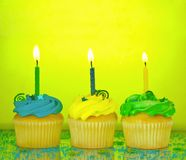 Birthday Cupcakes. Three birthday cupcakes in blue, green, and yellow with lit candles, confetti, and sprinkles on a mirrored background Royalty Free Stock Image