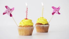 Birthday cupcakes with burning candle and pinwheel stock footage
