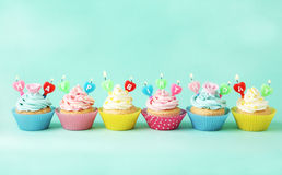 Birthday cupcakes with candles on green background Royalty Free Stock Images