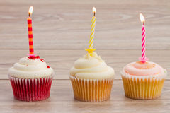 Birthday cupcakes on table. Birthday cupcakes with burning candles on wooden table Stock Image