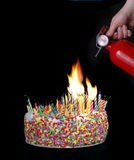 Birthday Disaster. A hand holding a fire extinguisher above a cake with candles creating a fire stock image