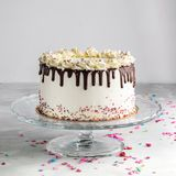 Birthday Drip Layered Cake with chocolate ganache and sprinkles on a white background with party decor. stock images
