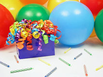 Birthday Gift. Wrapped birthday gift with curling ribbons, a balloon background and scattered birthday candles for making birthday cards, scrapbooking, or Stock Photography