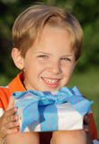 Birthday Gift. Happy young boy sitting and holding a gift outdoors Stock Photography