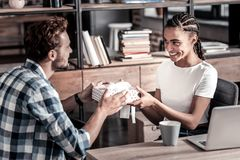 Cheerful positive woman receiving a present. Birthday gift. Cheerful positive nice women smiling and looking at her boyfriend while receiving a gift from him Royalty Free Stock Image