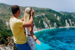 Birthday gift. Young man closing hes girlfriend eyes in front of gorgeous seascape panorama of blue lagoon. Couple love. Birthday gift. Young men closing hes stock photos