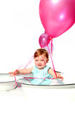 Birthday girl. Baby girl sitting in an enamel dish with pink helium balloons in the background royalty free stock photography