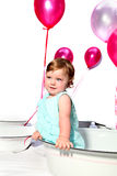 Birthday girl. Baby girl sitting in an enamel dish with pink helium balloons in the background royalty free stock photo