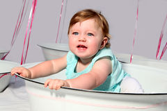 Birthday girl. Baby girl sitting in an enamel dish with pink helium balloons in the background stock photos