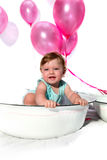 Birthday girl. Baby girl sitting in an enamel dish with pink helium balloons in the background royalty free stock photos