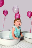 Birthday girl. Baby girl sitting in an enamel dish with pink helium balloons in the background royalty free stock images