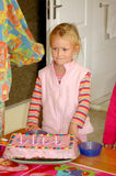 Birthday girl. A beautiful caucasian white girl child with a little bit embarrassed expression in her pretty face standing in front of her colorful delicious Stock Image