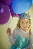 Birthday Girl With Balloons. A happy, smiling, birthday girl, with blond hair and blue eyes, dressed in a costume as a princess and wearing a sparkling crown stock photos