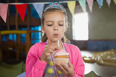 Birthday girl blowing candle on a cupcake Royalty Free Stock Photo