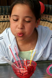 Birthday girl blowing out candles Stock Photo